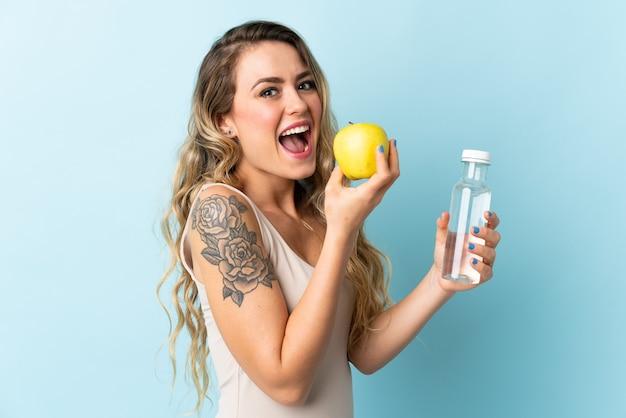 사과와 물 한 병 블루에 고립 된 젊은 브라질 여자