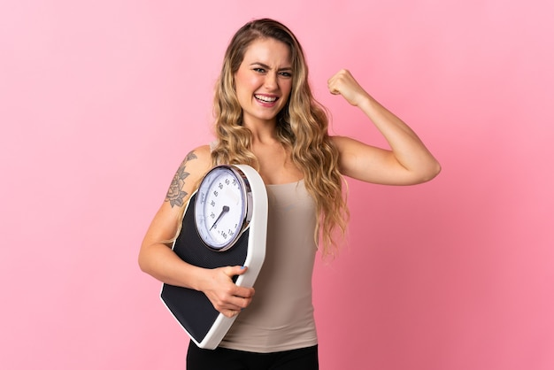 Молодая бразильская женщина изолирована на розовом, держит весы и делает сильный жест