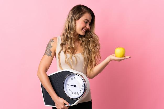 사과를 보면서 무게 기계를 들고 핑크에 고립 된 젊은 브라질 여자
