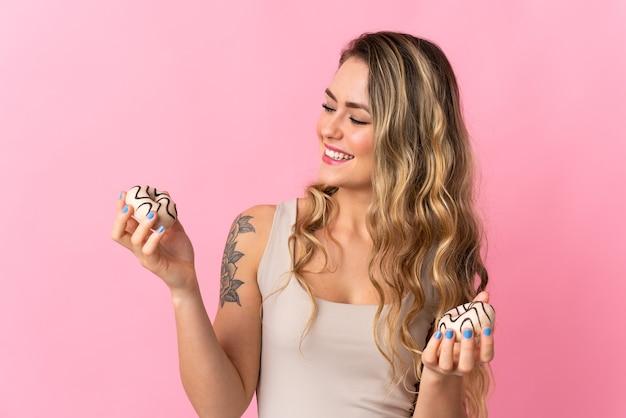 幸せな表情でピンクの持株ドーナツに分離された若いブラジル人女性