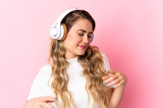 Молодая бразильская женщина изолирована на розовом, слушает музыку и танцует