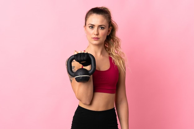 Молодая бразильская женщина, изолированная на розовом, делает тяжелую атлетику с гирями и смотрит вперед