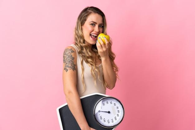 Молодая бразильская женщина изолирована на розовой стене с весами и яблоком