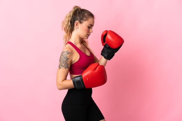 Молодая бразильская женщина изолирована на розовом в боксерских перчатках