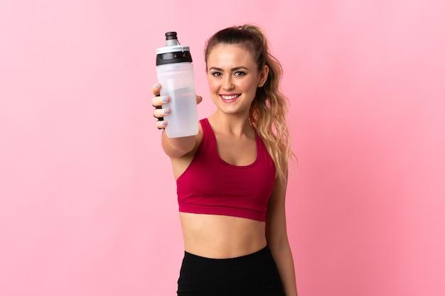 スポーツの水のボトルとピンクに分離された若いブラジル人女性