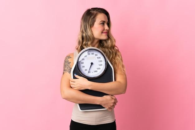 マシンの重量を量ると側を見てピンクに分離された若いブラジル人女性