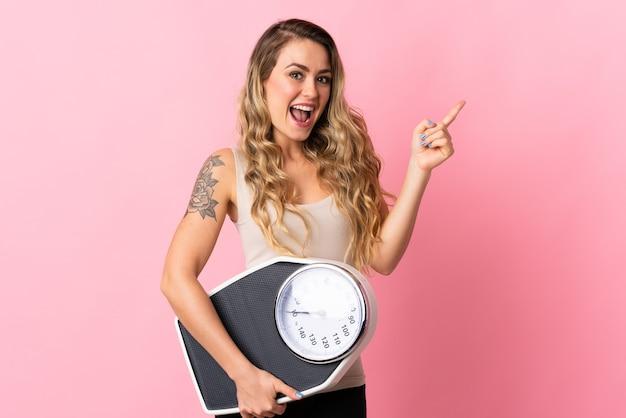 Молодая бразильская женщина изолирована на розовом с весами