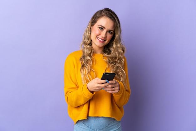 Молодая бразильская женщина изолирована на фиолетовом фоне, отправляя сообщение с мобильного телефона