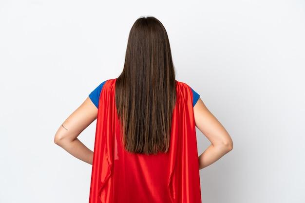 Молодая бразильская женщина изолирована на белом фоне в костюме супергероя в заднем положении