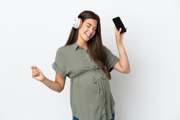 흰색 배경에 고립 된 젊은 브라질 여자 임신과 음악을 들으면서 춤