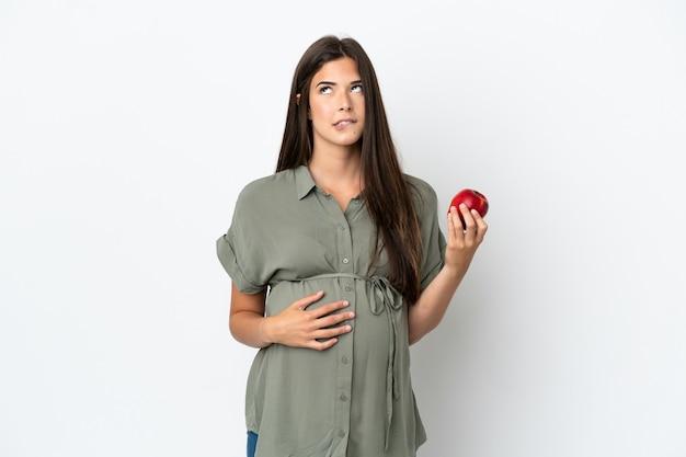 Молодая бразильская женщина изолирована на белом фоне беременной и разочарованной, держа в руках яблоко