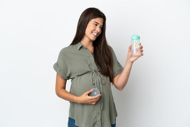 妊娠し、哺乳瓶を保持している白い背景で隔離の若いブラジル人女性