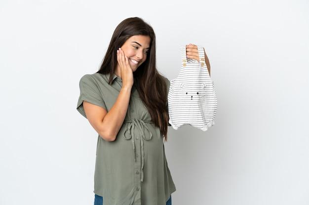 妊娠し、赤ちゃんの服を保持している白い背景で隔離の若いブラジル人女性