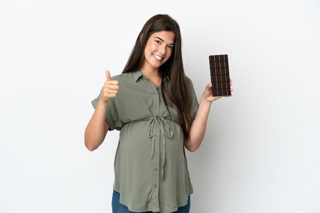 Молодая бразильская женщина изолирована на белом фоне беременной и держит шоколад с большим пальцем вверх
