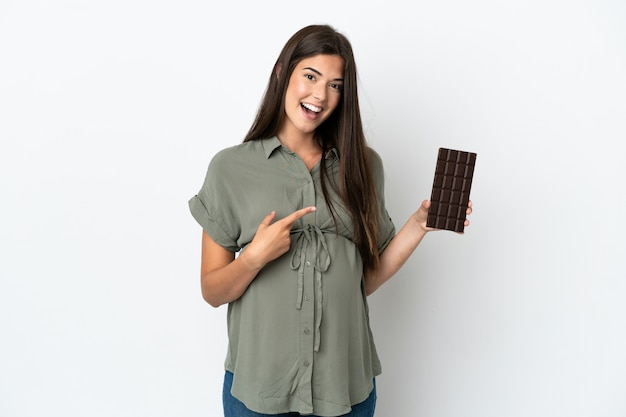 Молодая бразильская женщина изолирована на белом фоне беременной и держит шоколад