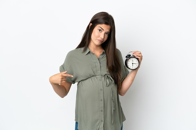 흰색 배경에 고립 된 젊은 브라질 여자 임신 및 스트레스 식으로 시계를 들고