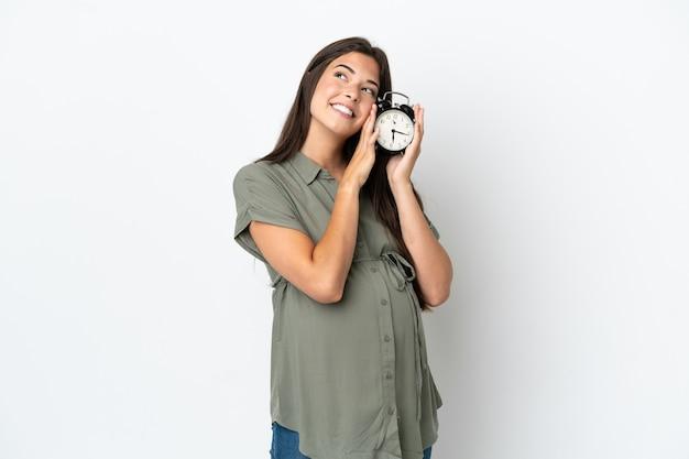 妊娠中と時計を保持している白い背景で隔離の若いブラジル人女性