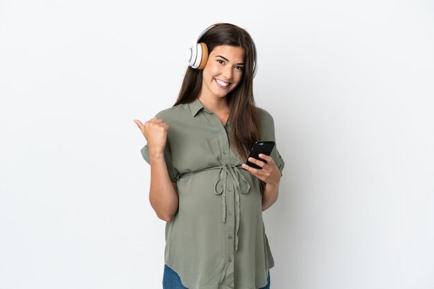 흰색 배경에 고립 된 젊은 브라질 여성 임신 및 측면을 가리키는 동안 음악을 듣고