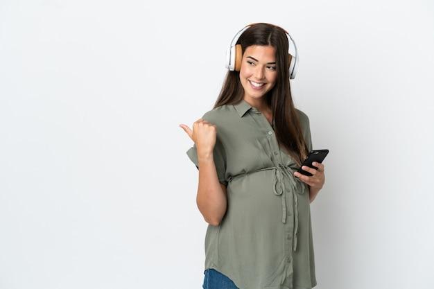妊娠し、側を指して音楽を聴いて白い背景で隔離の若いブラジル人女性