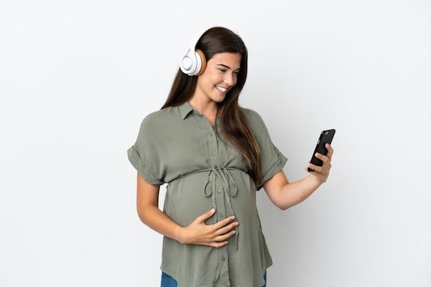 妊娠中の白い背景で隔離され、携帯電話で音楽を聴いている若いブラジル人女性