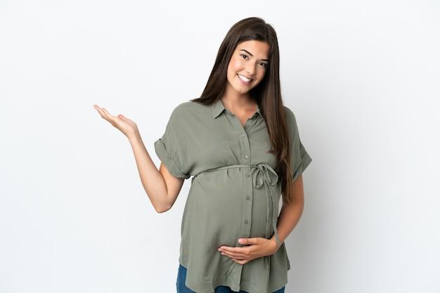 妊娠し、何かを提示する白い背景で隔離の若いブラジル人女性