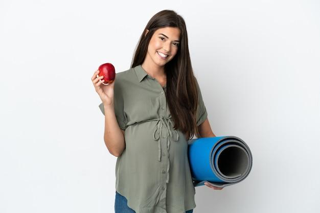 Молодая бразильская женщина изолирована на белом фоне беременная держит яблоко и собирается на занятия йогой