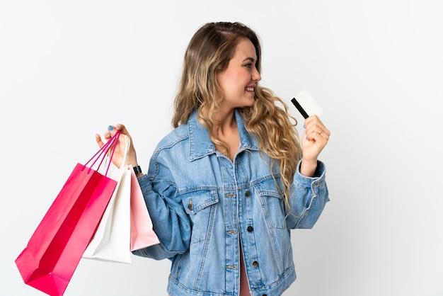 ショッピングバッグとクレジットカードを保持している白で隔離される若いブラジル人女性