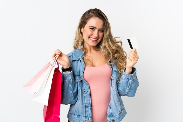 ショッピングバッグとクレジットカードを保持して白で隔離の若いブラジル人女性