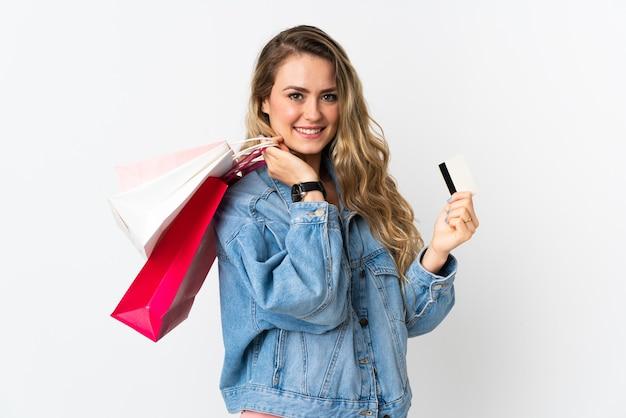 ショッピングバッグとクレジットカードを保持している白で隔離の若いブラジル人女性