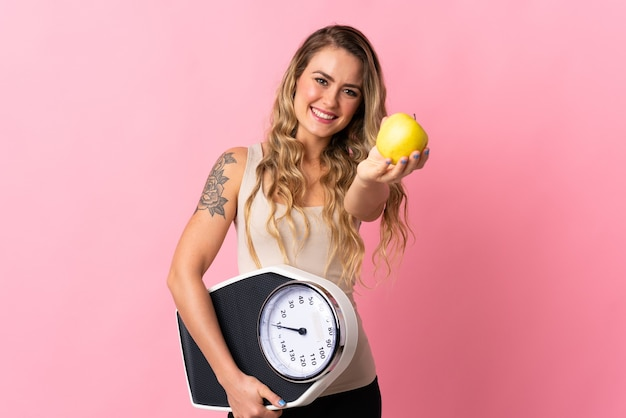 Young brazilian woman isolated on  pink holding weighing machine and offering an apple