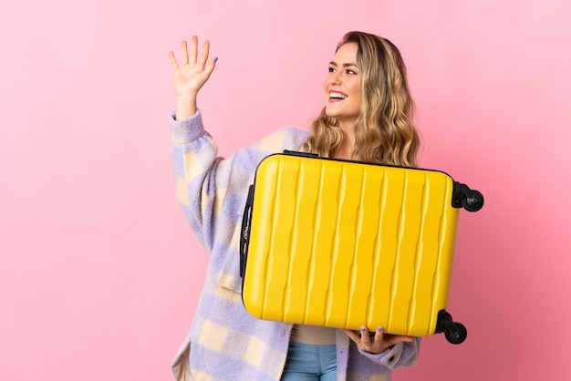 Young brazilian woman isolated on pink in vacation with travel suitcase and saluting