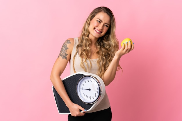 Young brazilian woman isolated on  pink with weighing machine and with an apple