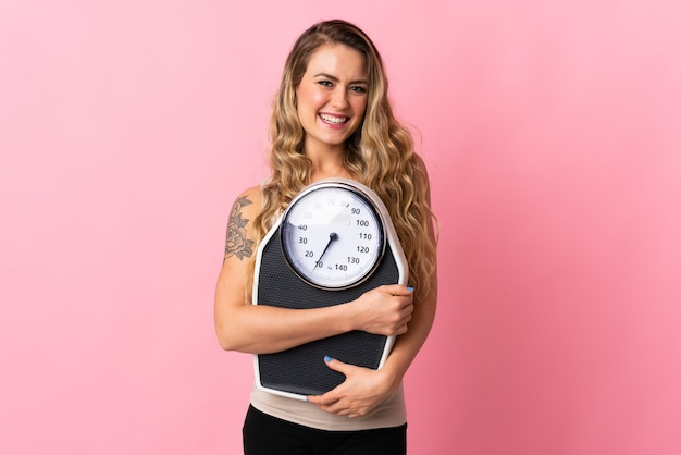 Young brazilian woman isolated on  pink with weighing machine