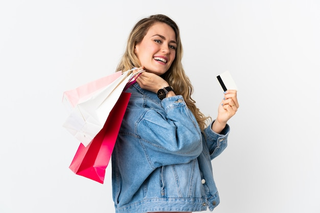 Young brazilian woman isolated on white holding shopping bags and a credit card