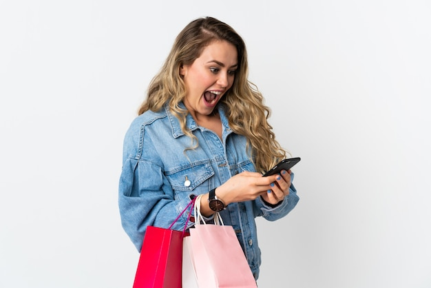 Young brazilian woman isolated on white holding shopping bags and writing a message with her cell phone to a friend