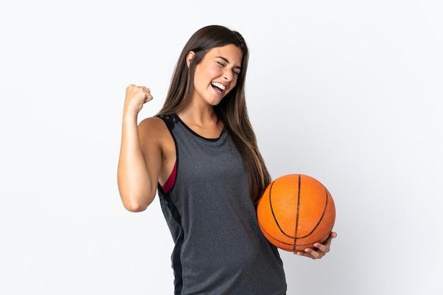 勝利を祝って白い背景で隔離のバスケットボールをしている若いブラジル人女性