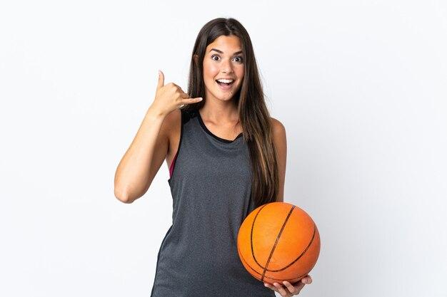 電話のジェスチャーを作る白い壁に分離されたバスケットボールをしている若いブラジル人女性。コールバックサイン