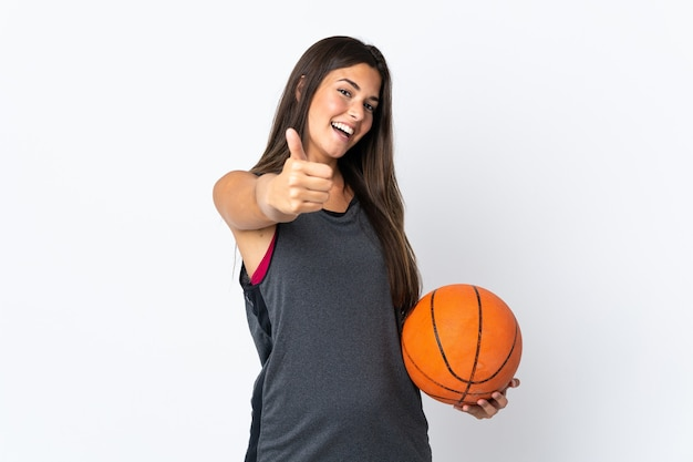 Молодая бразильская женщина играет в баскетбол изолирована на белой стене с большими пальцами руки вверх, потому что произошло что-то хорошее