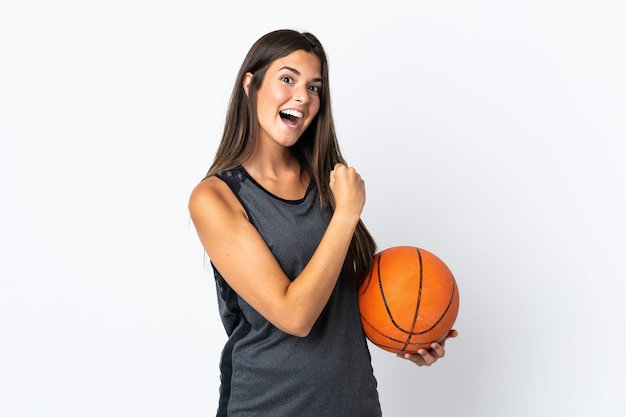 Young brazilian woman playing basketball isolated on white background celebrating a victory