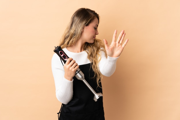 Young brazilian woman using hand blender isolated on beige making stop gesture and disappointed