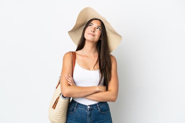 Молодая бразильская женщина с памелой, держащей пляжную сумку на белом фоне, глядя вверх, улыбаясь