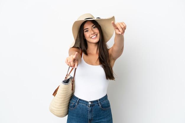 Молодая бразильская женщина с памелой, держащей пляжную сумку на белом фоне, показывает пальцем на вас, улыбаясь