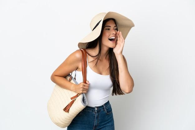 Молодая бразильская женщина с памелой, держащей пляжную сумку на белом фоне, кричит с широко открытым ртом