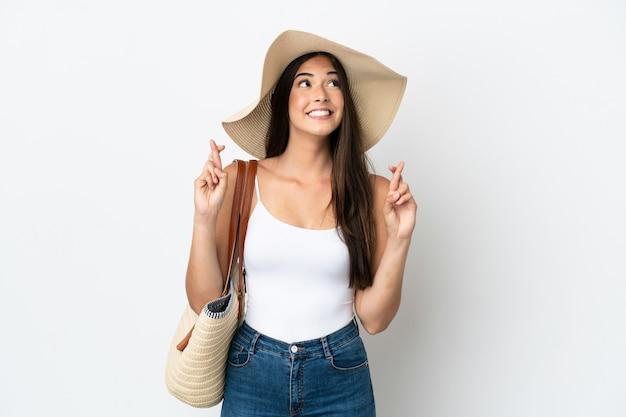 Молодая бразильская женщина с памелой, держащей пляжную сумку на белом фоне со скрещенными пальцами