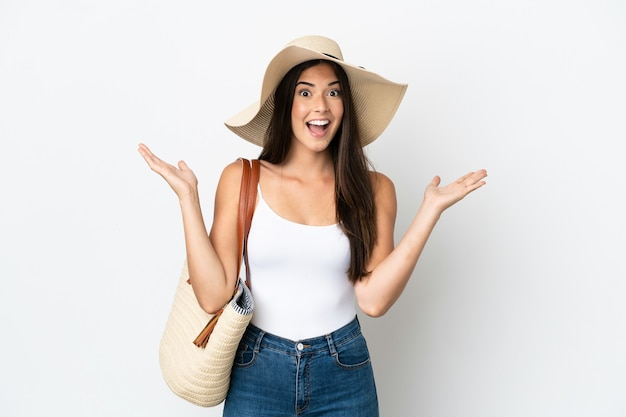 Young brazilian woman with pamela holding a beach bag isolated on white background with shocked facial expression
