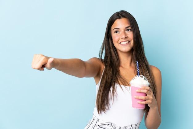 Молодая бразильская женщина с клубничным молочным коктейлем на синем фоне показывает палец вверх