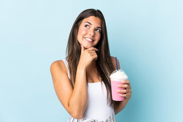 笑顔で見上げる青い壁に分離されたイチゴのミルクセーキと若いブラジル人女性