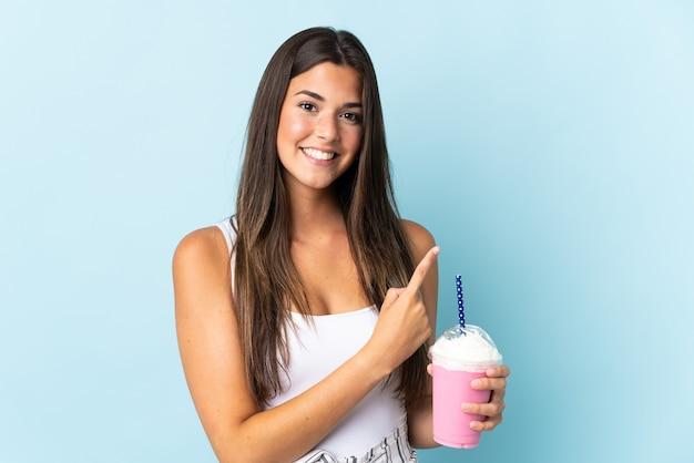製品を提示する側を指している青い壁に分離されたイチゴのミルクセーキと若いブラジル人女性