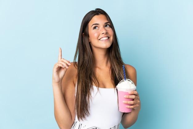 素晴らしいアイデアを指している青い壁に分離されたイチゴのミルクセーキと若いブラジル人女性