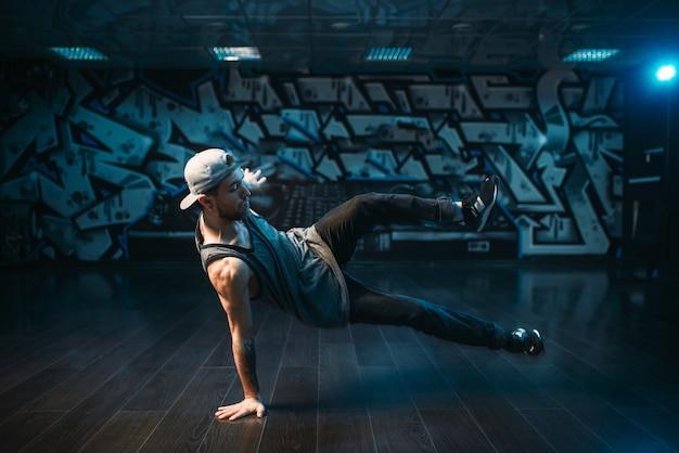 Молодой исполнитель брейк-данса танцует в студии. современный городской танцевальный стиль. мужчина танцор
